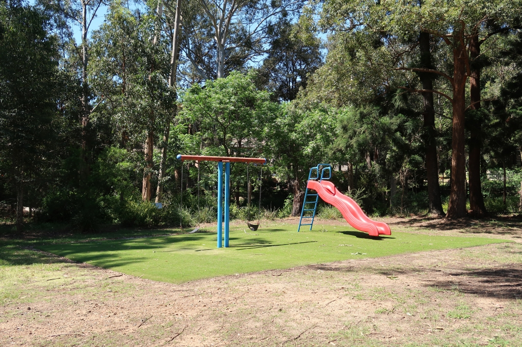 Tiny playground with two swings and a slide, surrounded by trees and carpeted with artificial grass.